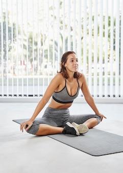 Женщина в полный рост на коврике для йоги