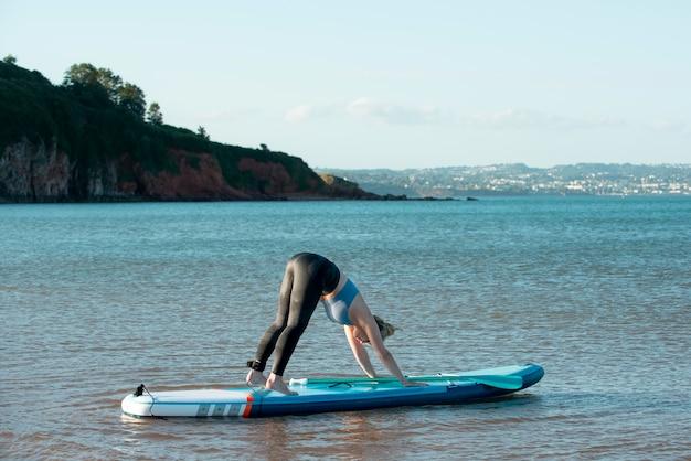 Full shot woman on paddleboard