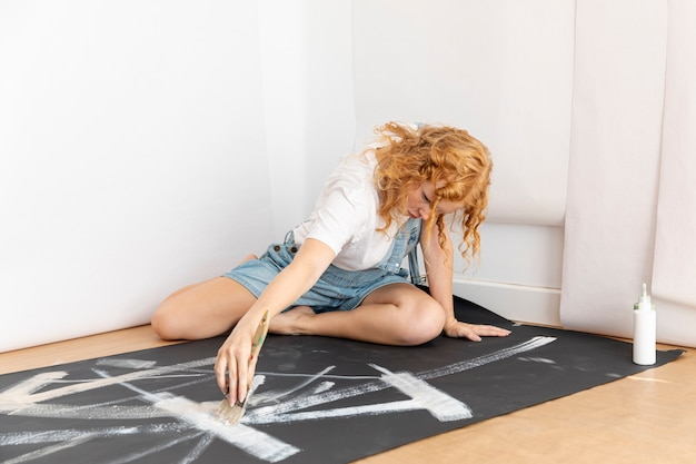 Full shot woman painting with white paint