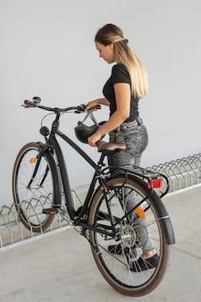 Full shot donna parcheggio bici