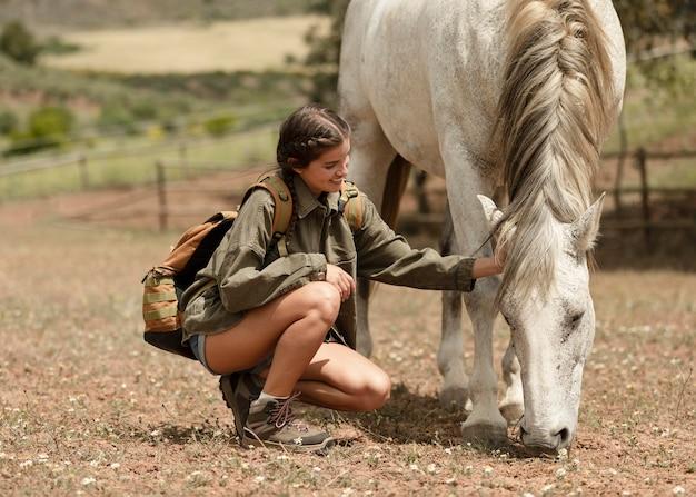 Full shot woman petting horse