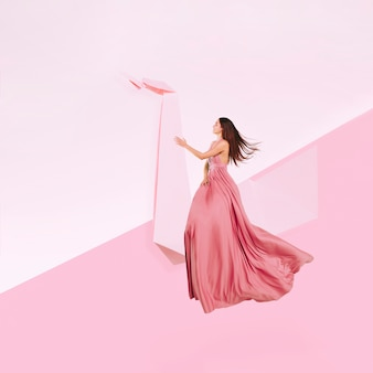 Full shot woman in pink dress levitating