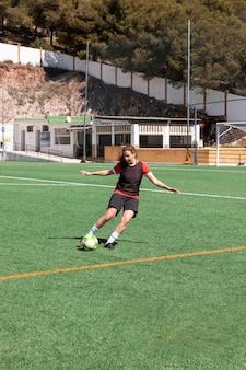 Полный выстрел женщина играет в футбол на открытом воздухе