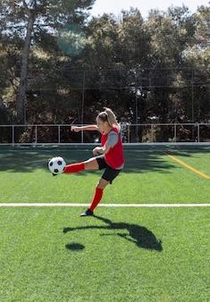 サッカーをしているフルショットの女性