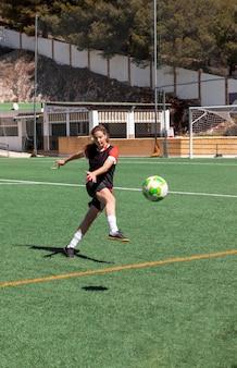 Полный выстрел женщина играет в футбол