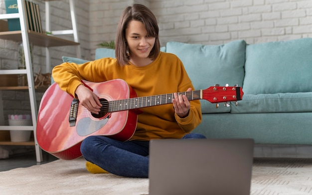 Full shot woman playing guitar at home