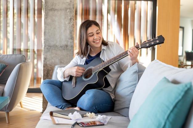 Donna piena del colpo che gioca la chitarra