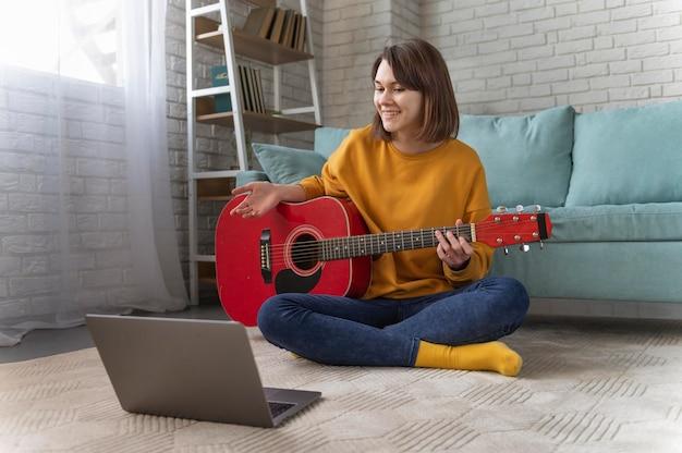 ギターを弾くフルショットの女性