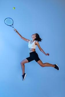라켓으로 테니스를 치는 전체 샷 여자