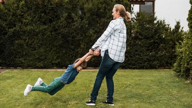 Женщина в полный рост, играя с ребенком