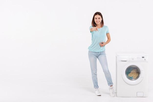 Donna della foto a figura intera che indica alla macchina fotografica con copia-spazio