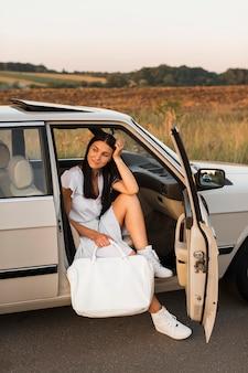 車でポーズをとるフルショットの女性