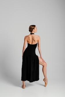 Полный выстрел женщина позирует в платье