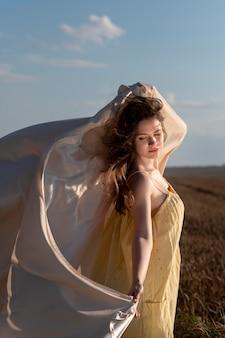 自然の中でポーズをとるフルショットの女性