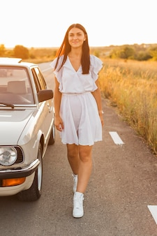 Donna del colpo pieno che posa vicino all'automobile