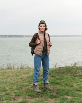 水の近くでポーズをとるフルショットの女性