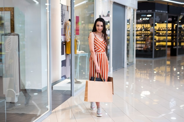 Full shot woman posing outside the store