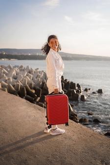 Donna del colpo pieno che posa con i bagagli