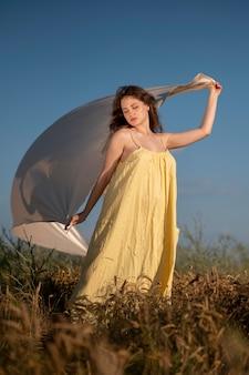 布でポーズをとるフルショットの女性