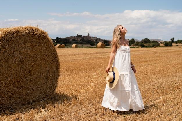 帽子をかぶってポーズをとるフルショットの女性