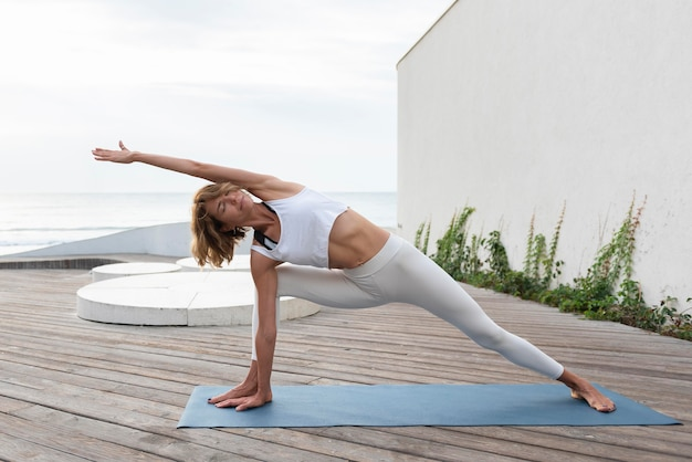 Full shot woman practicing yoga on mat outdoor