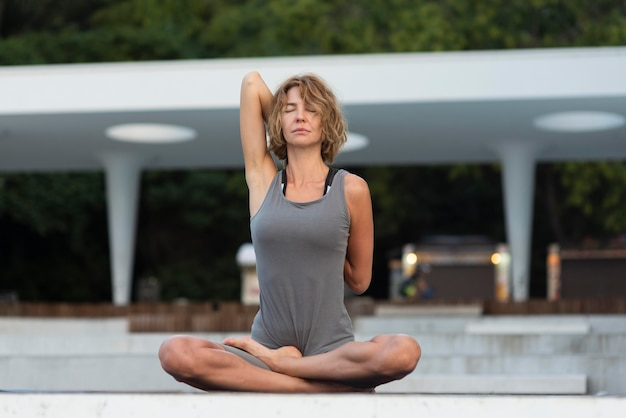 Full shot woman practicing yoga on mat outside