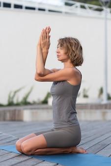 Donna piena del colpo che pratica yoga fuori sulla stuoia