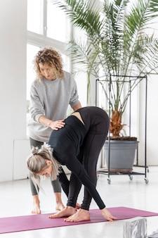 Полный снимок женщины, практикующей йогу с учителем