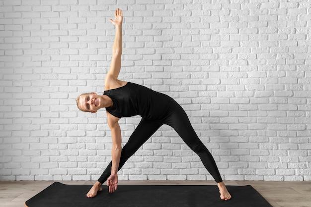 Полный снимок женщины, практикующей йогу