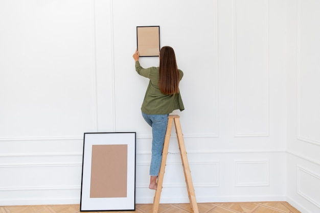 Full shot woman putting frame on wall
