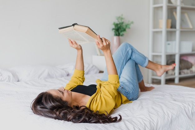 Full shot woman reading in bed