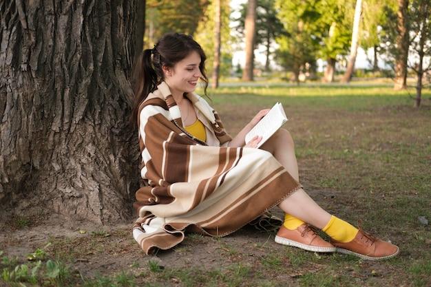 Полный выстрел женщина, читающая книгу