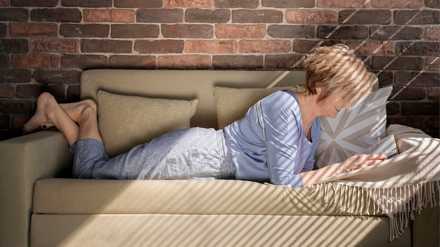 Full shot woman reading on couch