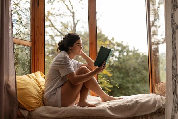 Полный снимок женщины, читающей в постели