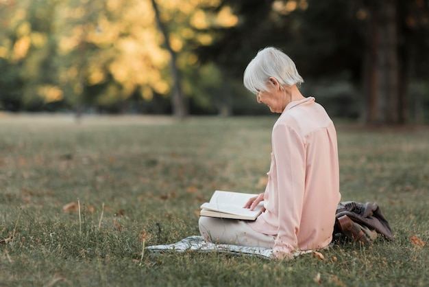 Полный снимок женщины, читающей на природе