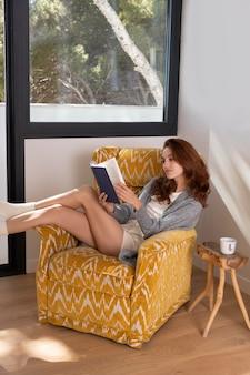 Полный снимок женщина, читающая на кресле