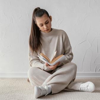 Полный выстрел женщина, читающая на полу
