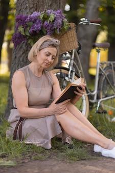 Полный снимок женщина, читающая на открытом воздухе