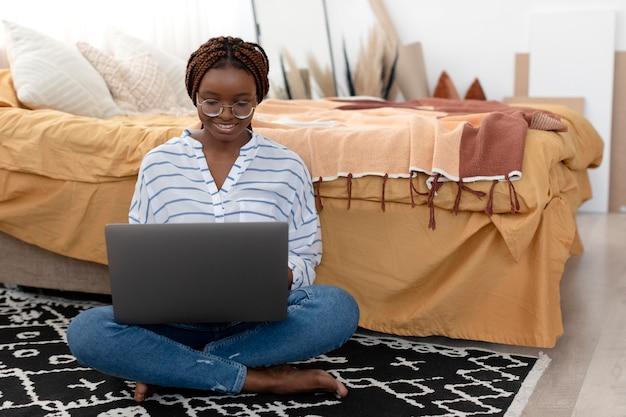 Donna a tutto campo che si rilassa con il laptop