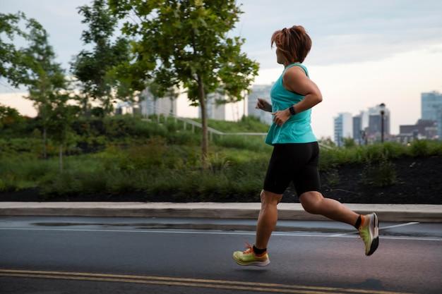 屋外で走っているフルショットの女性