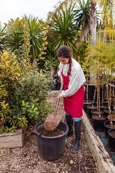 Full shot woman shoveling in large flower pot