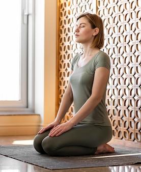 Женщина в полный рост сидит и медитирует