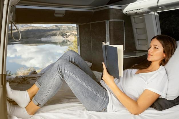 Женщина в полный рост сидит и читает
