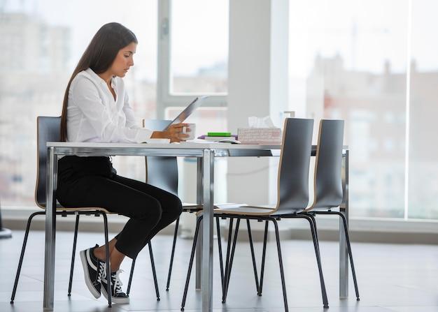 Полный снимок женщина, сидящая за столом