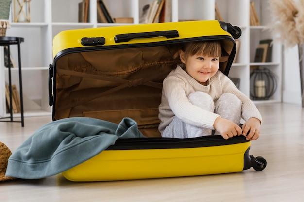 Donna piena del colpo che si siede nel bagaglio