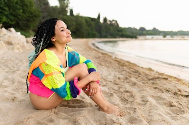 Donna della foto a figura intera che si siede sulla spiaggia
