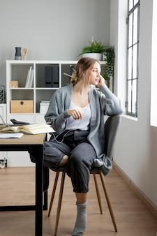 Donna piena del colpo che si siede sulla sedia