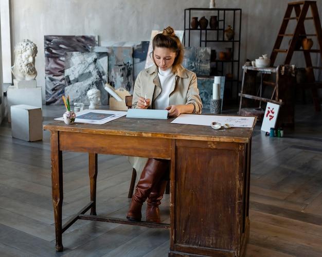 Donna piena del colpo che si siede allo scrittorio