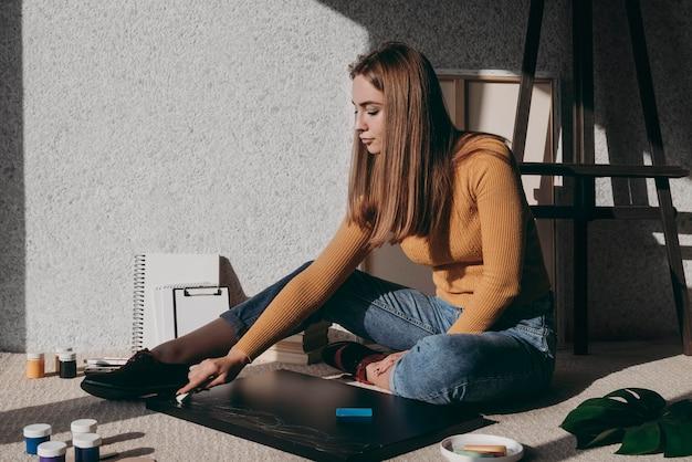 Donna piena del colpo che si siede sul pavimento