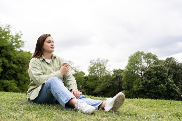 Full shot woman sitting on grass